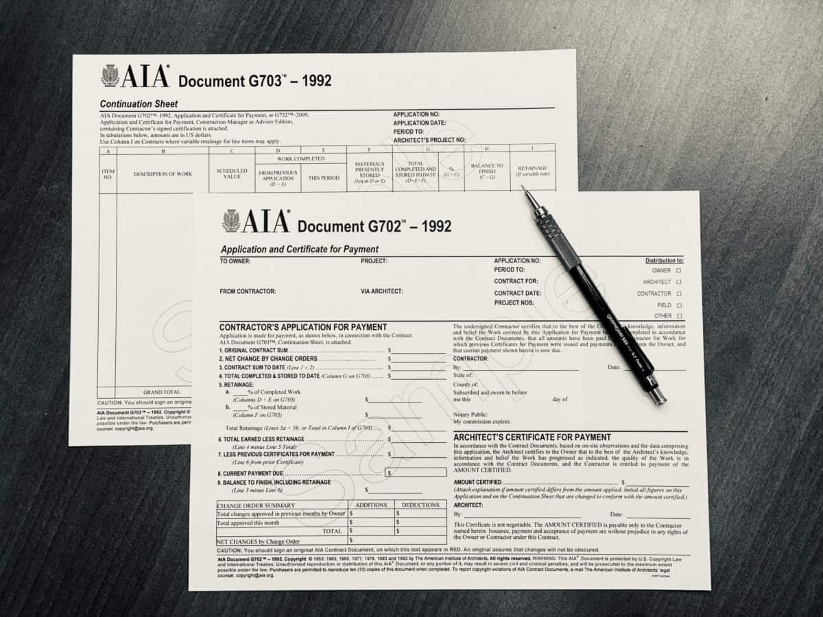 AIA G702 and G703 billing forms on a desk