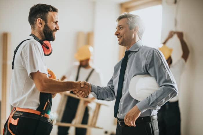 construction site manager and client shaking hands after discussing change orders