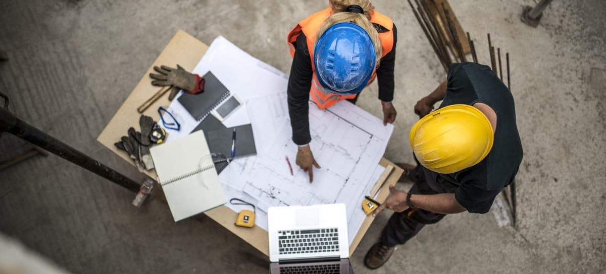 two professionals at a construction site managing the details of a change order on a blueprint and a computer