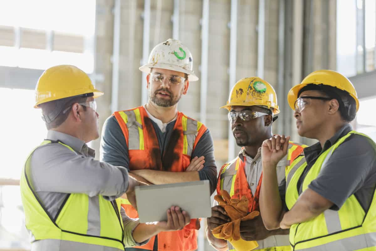Construction workers looking at a digital tablet with pay app process instructions