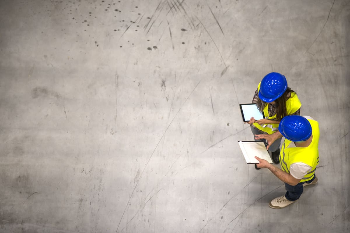 Two construction site managers approving invoices through an app