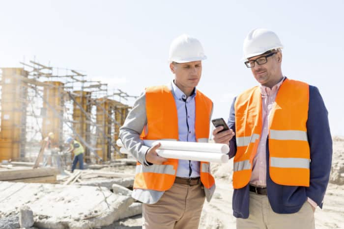 Two construction workers recording data for AIA G702/G703 forms with an on-site mobile device