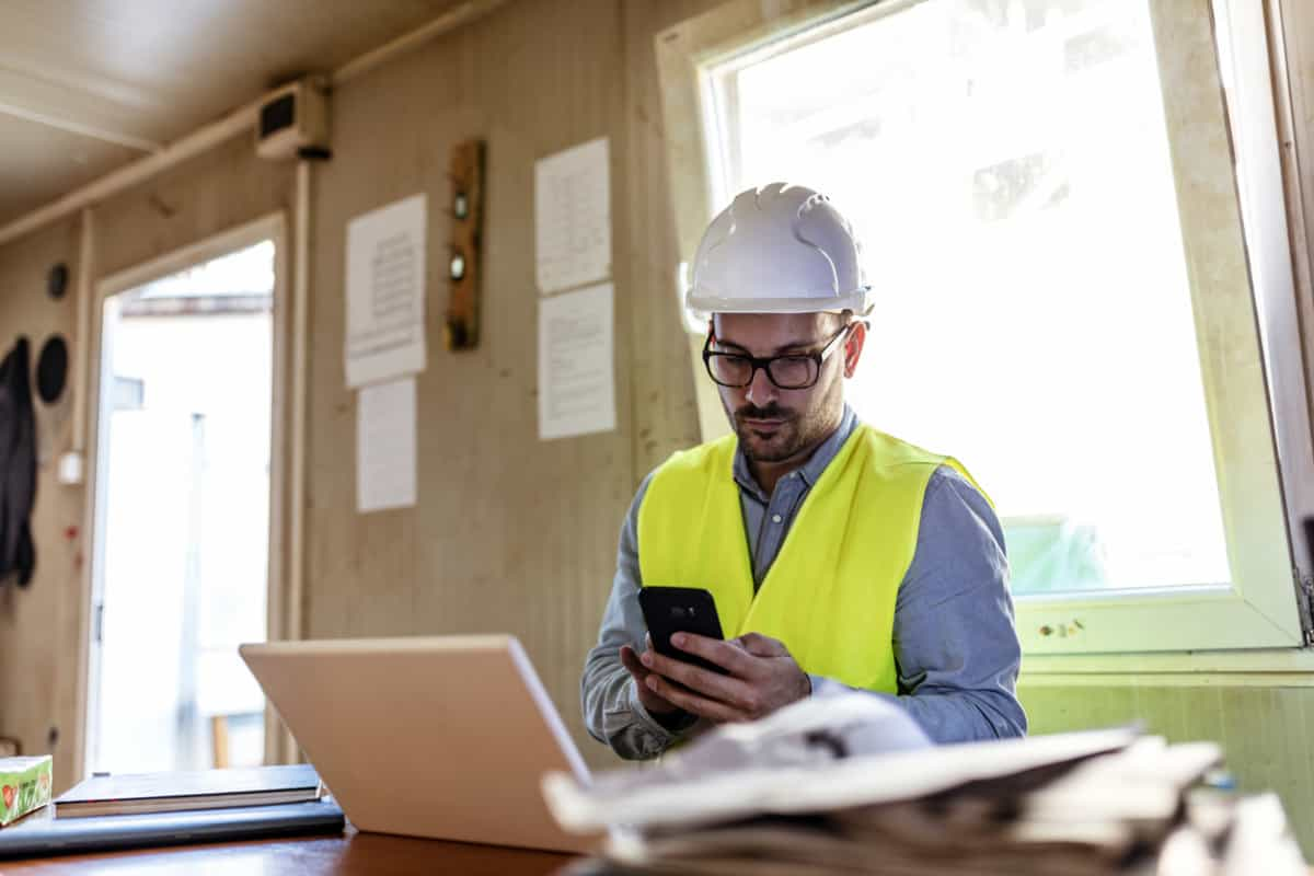 Construction site manager managing paperwork and digital Georgia lien waiver forms