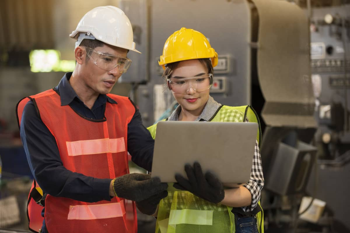 Construction company employees navigating a new ERP system on a laptop