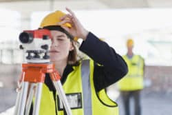 Entry-level construction worker starting to survey a project