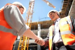 Second tier and first subcontractors shaking hands after signing a subcontractor agreement