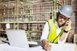 General contractor managing construction billing forms over the phone and computer