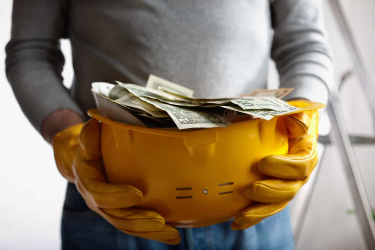 A Construction Worker Holding a Hard Hat full of Money